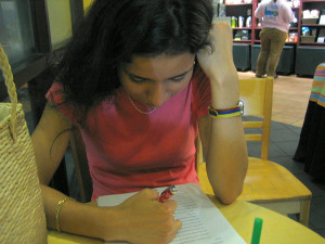 Woman reviewing an essay with a pen in her hand at a coffee shop table