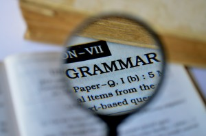 """magnifying glass held over the word """"grammar"""" in a dictionary"""