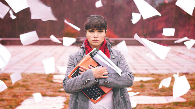 Woman holding an orange typewriter, staring at the camera, while sheets of paper blow in the wind around her