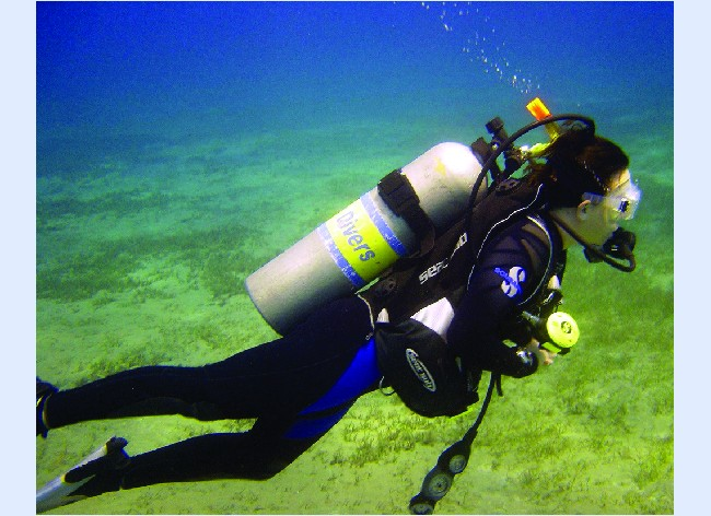 This photograph shows a scuba diver underwater with a tank on his or her back and bubbles ascending from the breathing apparatus.