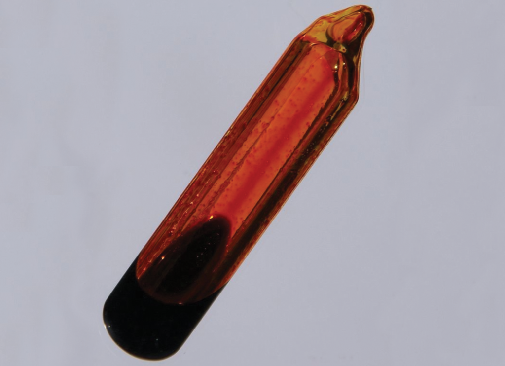 A glass container is shown that is filled with an orange-brown gas and a small amount of dark orange liquid.