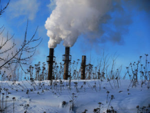 Photo of snowy landscape with three factory chimneys on the horizon, filling the air with smoke.