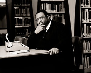 Photo of a man sitting in an office or library with a small typewriter on the table. His head rests on his hand, and he looks contemplative.