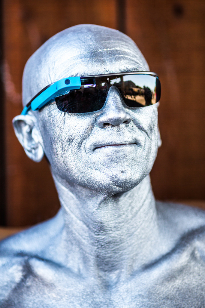 A bald man, whose entire head, face, and neck are covered in silver paint, wears a pair of Google Glass glasses and smiles.