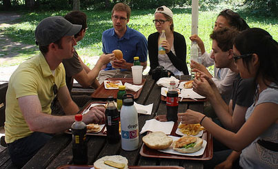 A group of people at a picnic table eating food