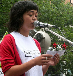 A woman reading a speech at a microphone