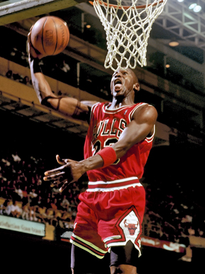 Michael Jordan in the air about to through the basketball through the hoop