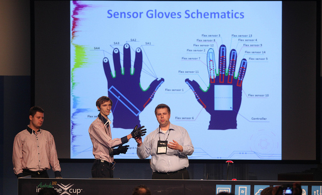 One man wears a sensor glove while another man points at the glove and speaks into a microphone. Behind them is a large powerpoint slide showing schematics for the sensor glove.