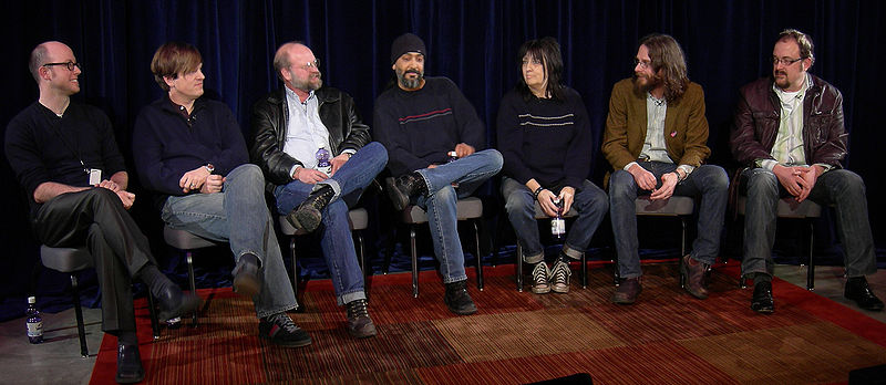 A row of people sitting in chairs on a stage