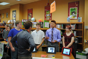 Four students giving a presentation in a library