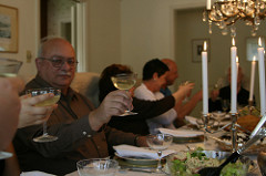 People sitting at a dinner table, holding their glasses in a toast