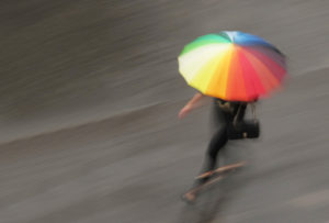 Photo of a woman running in the rain holding a rainbow-colored umbrella.