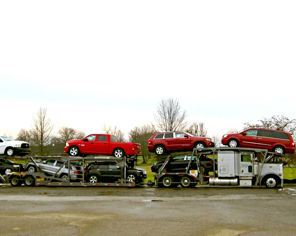 Large truck loaded with new cars.