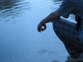 Photo of someone crouching beside a pond, apparently having just dropped a stone into the water. Concentric circles can be seen where the stone dropped in.
