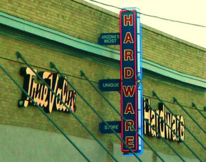 "Photo of a True Value Hardware store sign on the side of a brick building, with additional signage that reads, ""Arizona's most unique store."""