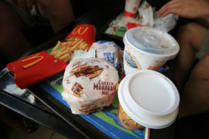 "Photo of a plastic food tray with McDonald's fries, two drinks, a regular burger, and a chicken ""Maharaja Mac."""