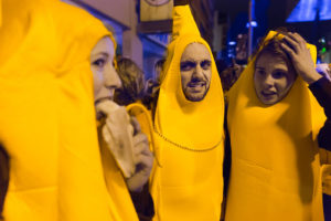 Three people wearing banana costumes