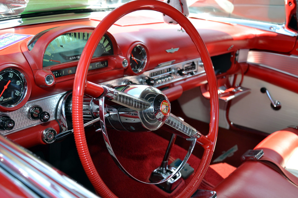 Photo of the steering wheel and dashboard of a classic automobile.