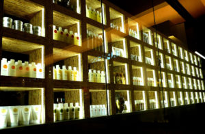 Rows of fancy hair products shown on backlit glass shelves.