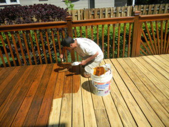 Photo of a man brushing wood stain on a new wooden deck.