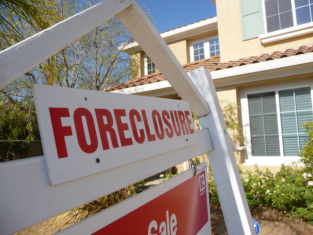 """A house with a """"foreclosure"""" sign in the foreground"""