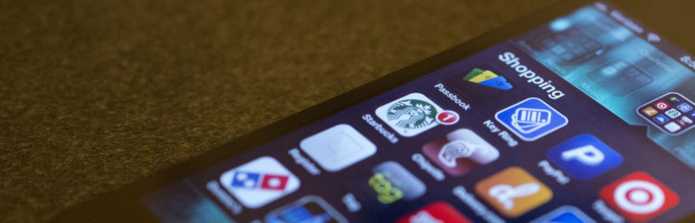 Photo of a smartphone screen, showing a screenful of online shopping options (e.g., Starbucks, Dominoes Pizza, etc.).