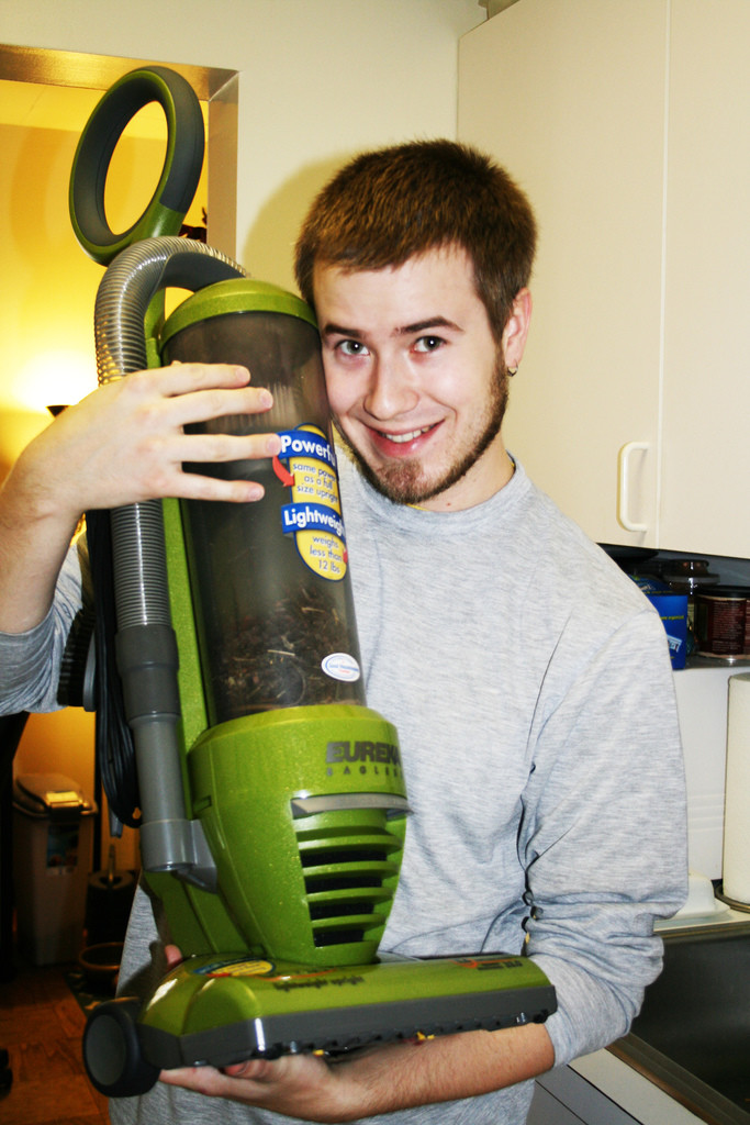 Young man holding a green vacuum cleaner and smiling