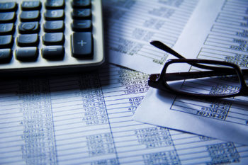 Photo of calculator, balance sheets, a pair of reading glasses
