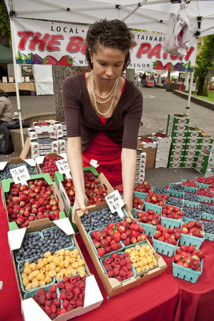 A woman adjusts baskets of berries at a stand in a farmer's market.