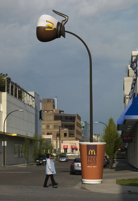 A man walks by an odd lamppost. The bulb of the light looks like a McDonald's coffeepot, while the base of the lamp looks like a McDonald's coffee cup. The pole of the lamppost looks like coffee being poured from the coffeepot into the cup.