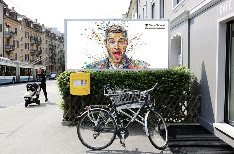 A billboard for ClearChannel. It depicts a bright and colorful mosaic that forms a portrait of an excited man.