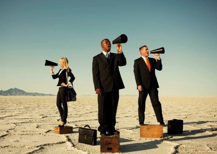 Three businesspeople stand in the middle of the desert, their briefcases at their feet. Each businessperson is shouting into a megaphone in different directions.