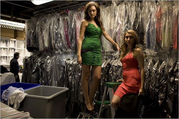 Jennifer Carter Fleiss and Jennifer Hyman wearing evening dresses in front of racks of dresses