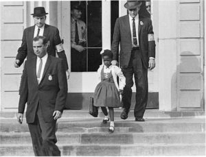 Photo of U.S. marshals with young Ruby Bridges on the steps of the William Frantz Elementary School.