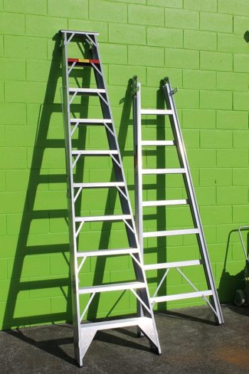 Photo of two ladders leaning against a green wall.