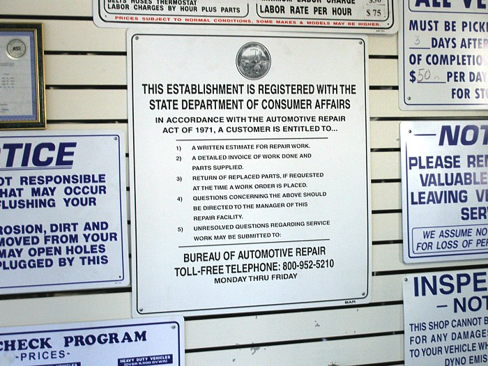 Consumer protection sings on display in an automotive repair shop