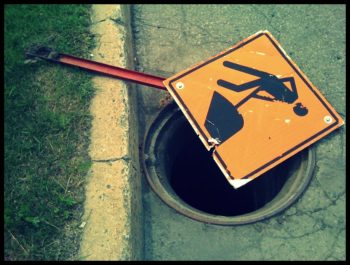 "Photo of a hole in street (without its manhole cover), partially covered by a ""men at work"" street sign. Photo tag: ""lawsuit waiting to happen."""
