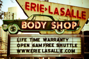 """Photo of neon sign for Erie LaSalle Body Shop. The marquee reads, """"Life time warranty, open 6am, free shuttle, www.erielasalle.com"""""""