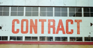 Photo of the side of an old brick building with a large white sign that reads CONTRACT in orange letters