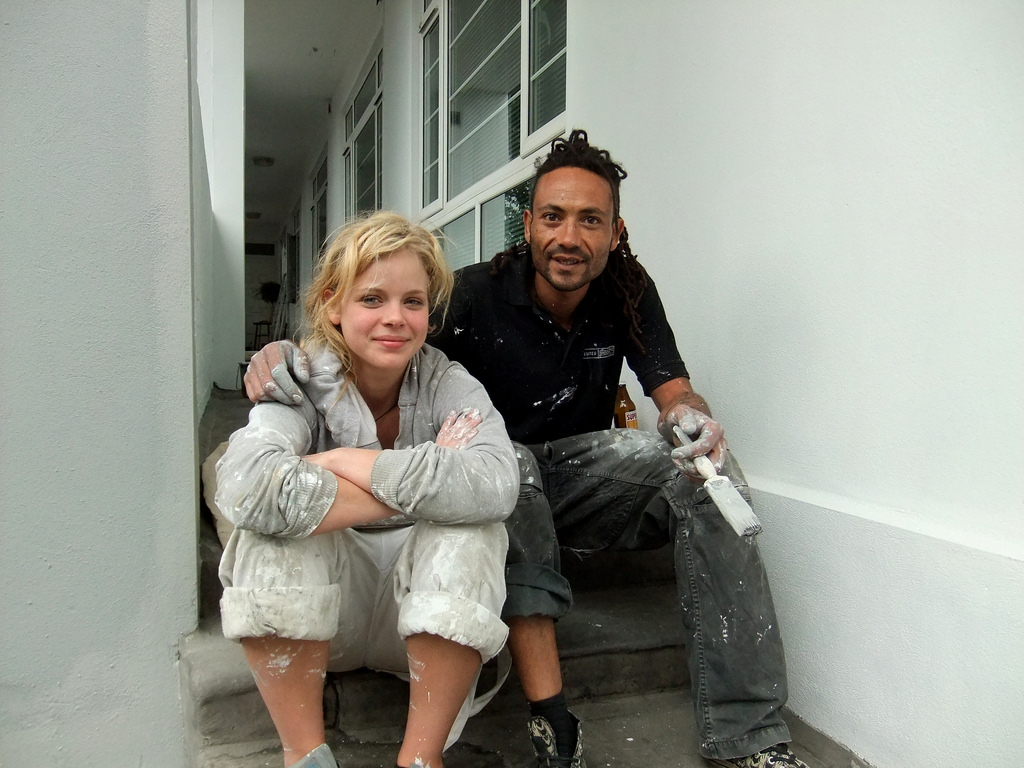 a man and a woman both wearing paint-covered overalls