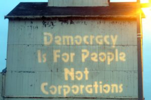 """Photo of an old building with the words """"Democracy Is For People, Not Corporations"""" painted in yellow."""