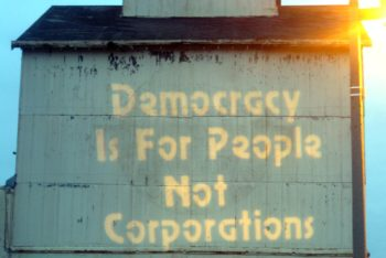 "Photo of an old building with the words ""Democracy Is For People, Not Corporations"" painted in yellow."