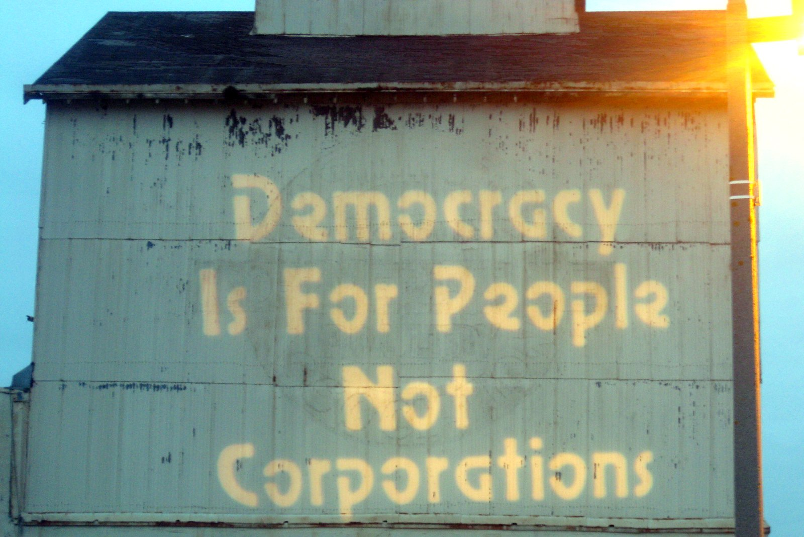 """An old building with the words """"Democracy Is For People, Not Corporations"""" painted on it"""