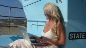 Photo of woman sitting on a boat working on her laptop.