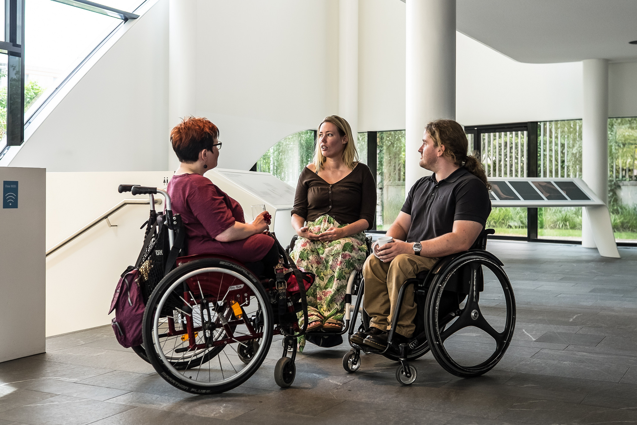 Three women in wheelchairs confer in a large office space.
