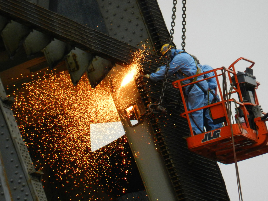 Photo of a construction worker on the side of a building, welding. Bright sparks fly.