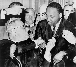 President Lyndon Johnson shakes hands with Martin Luther King Jr. after presenting him with one of the pens used to sign the Civil Rights Act of 1964.