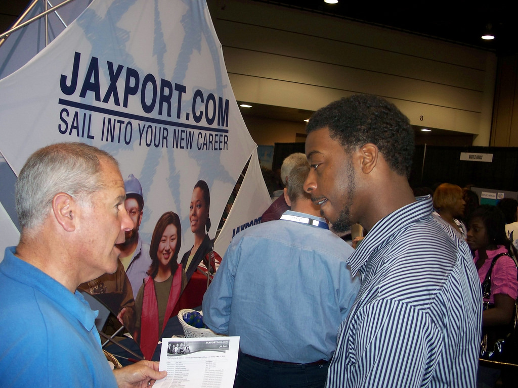 "A man talks to another, younger man at a job fair. In the background is a poster advertising Jaxport.com. ""Sail into your new career."""