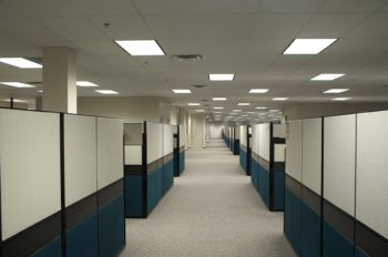 Photo of a completely empty office building with many rows of cubicles, also empty, shown after all the workers were laid off.