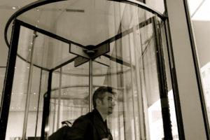 Photo of man exiting building through a revolving glass door at MOMA